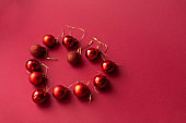 Red Christmas tree decorative toy balls on red celebratory Christmas background laid out in the shape of a heart. New Year's holidays. Christmas holidays