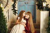 Cute little princess with mom hugging on the stairs. keep a rabbit in hands