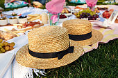 straw hats lay on a white picnic blanket at green lawn bright summer day background. Summer weekends leisure.