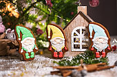 Holiday traditional food bakery. Four Gingerbread little fairytale gnomes in cozy decoration with garland lights