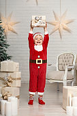 Happy little smiling boy in santa claus costume holds white christmas gift box.