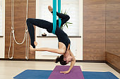 a group of women hang upside down in a hammock. fly yoga class in the gym. Fit and wellness lifestyle