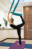Woman doing fly yoga stretching standing on one leg on the ground and second in hammock. Fit and wellness lifestyle.