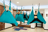 Women doing fly yoga stretching exercises in hammock. Fit and wellness lifestyle