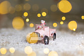 Decorative figurines of a Christmas theme. Santa statuette rides on a toy car with a trailer for gifts. Festive decor, warm bokeh lights.