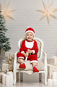 Happy little smiling boy in santa claus costume sitting on armchair near christmas tree and holding christmas gift box