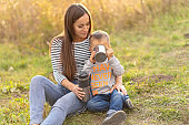 Happy family on autumn walk. Young beautiful mother with little son enjoy nature.