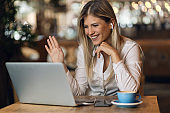 Happy businesswoman making a video call over laptop and waving to someone