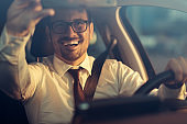 Happy businessman driving a car