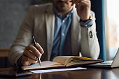 Close up of unrecognizable businessman taking notes in note pad