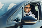 Smiling businessman driving a car and looking at side view mirror