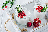 Christmas coconut punch with pomegranate seeds and sprigs of rosemary on light background. Selective fcus. Top view.