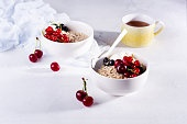 Raw oatmeal with yogurt and berries of cherry, currant and blueberry for making healthy breakfast in white ceramic bowl on a light background. Selective focus.