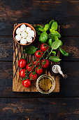 Fresh cherry tomatoes, basil leaves, mozzarella cheese and olive oil on old wooden background. Caprese salad ingredients. Selective focus.
