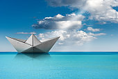 Paper boat in the turquoise sea with blue sky and clouds