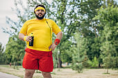 Overweight man drinking water after exercising