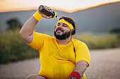 Overweight man pouring  water on his face