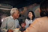 Three senior friends on coffee break in cafe