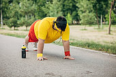 Overweight man doing pushups