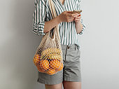 woman with mesh bag on shoulder using smartphone