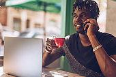 Handsome black guy on coffee break in cafe
