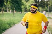Overweight man running in park