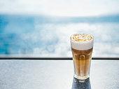 Latte macchiato coffee, sea background, copy space
