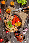 homemade hotdog sausages fried from red and white fish meat, in a vintage rustic plate bowl, fork knife spoon, spices, herbs, stand and lie, angles, on a wooden cutting board, dark light
