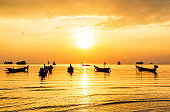 Longtail boat silhouettes at sea during golden sunset.