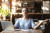 Young woman sitting at table in cafe relaxing do meditation