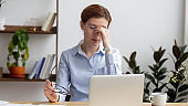 Tired businesswoman suffering from eyes strain, massaging nose bridge