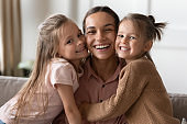 Happy mother and children daughters embracing looking at camera