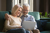 Smiling mature couple, wife and husband using laptop together at home