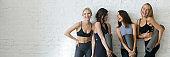 Horizontal image cheerful girls wearing activewear standing holding yoga mats