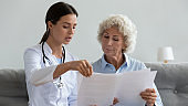 Serious young doctor explain insurance contract to elder grandma patient