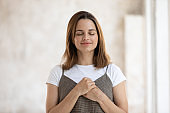 Portrait of grateful hopeful beautiful woman holding hands on chest