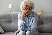 Depressed old woman sit on sofa suffering from headache grief