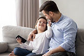 Loving father hugging little son, having fun together, using phone