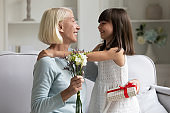 Happy preschool cute girl congratulating smiling middle aged grandmother.