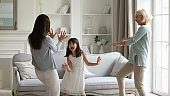 Overjoyed energetic little girl having fun with mother and granny.