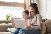 Happy mother and child daughter use laptop computer at home