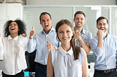 Portrait of excited employees posing with female team leader