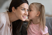 Little daughter telling secret to smiling mother, whispering in ear
