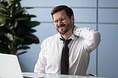 Tired male office worker suffer from backache at workplace