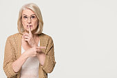 Old woman holding finger on lips pointing at copyspace isolated