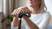 Old senior woman holding cane stick in hands, close up