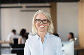 Cheerful senior businesswoman in glasses looking at camera in office