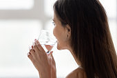 Young woman in bed drink pure water in morning