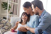 Happy family with kid cuddle on couch congratulating with birthday