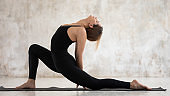 Young woman practicing yoga, standing in anjaneyasana pose, Horse rider